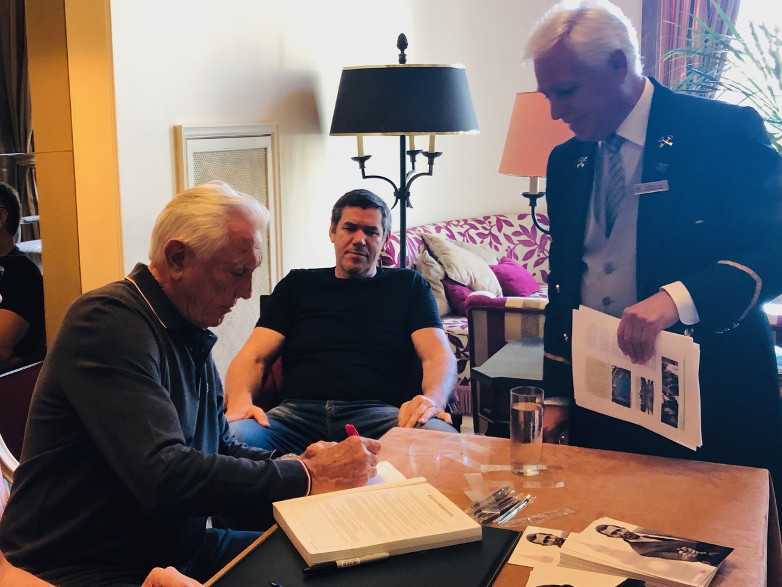 The Palacio's Head Concierge José Diogo gets an autograph from George Lazenby